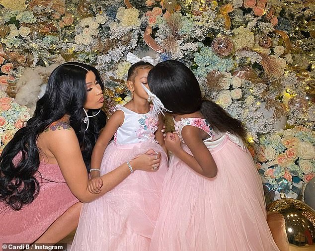 Family Time: WAP beat maker rang at Christmas surrounded by her family as Kulture opened gifts in a glittery dress