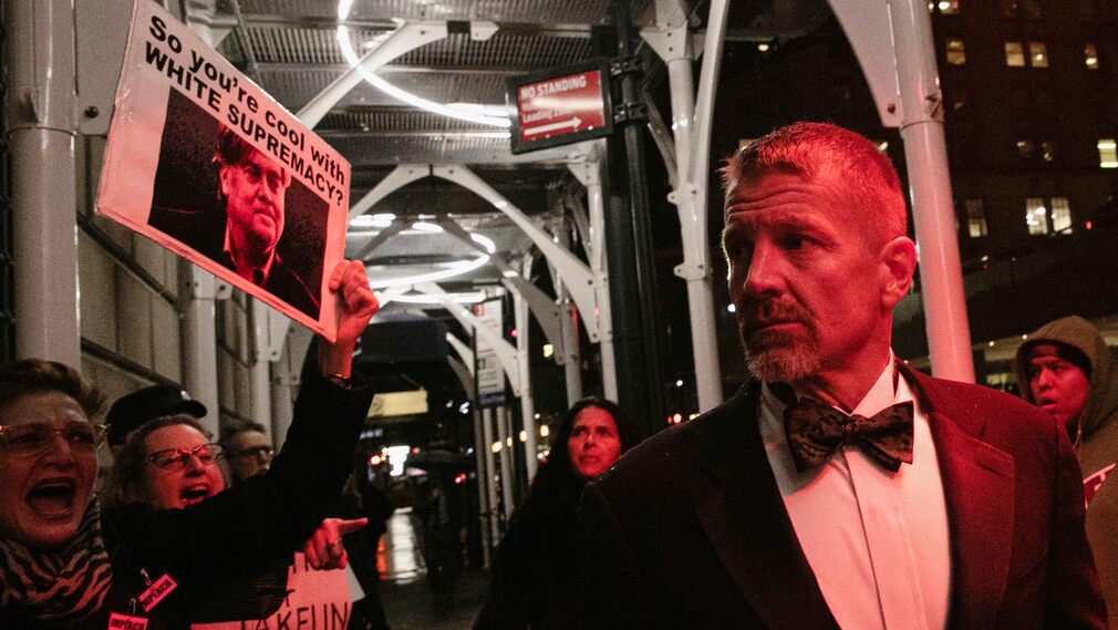 Eric Prince has striking resemblance to the blonde tuxedo and hitch of James Bond actor Daniel Craig.  But this does not impress the protesters appearing outside of Manhattan's Yale Club.  They harass Prince for his association with Trump adviser Steve Bannon.