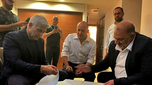 Mansour Abbas (right) of an Islamist signs the agreement with Yair Lapid (right).